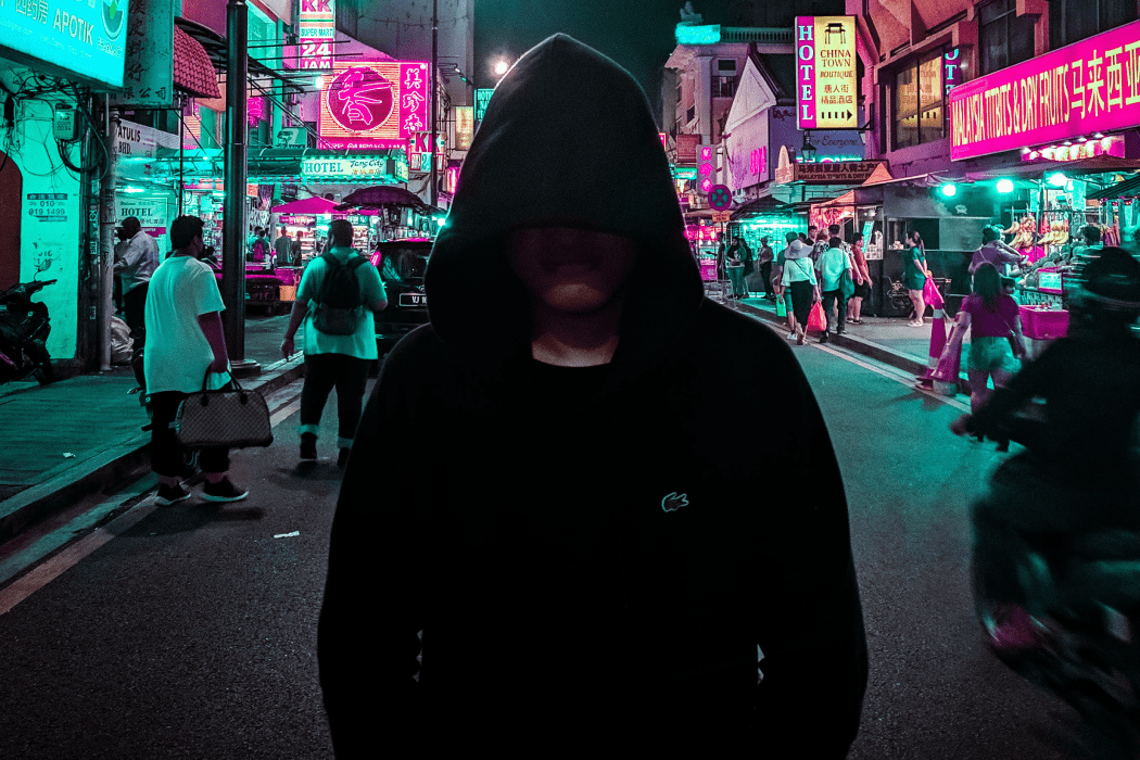 Hooded man standing in the middle of a street