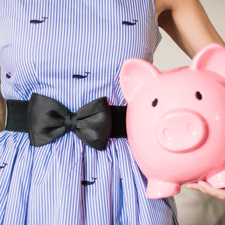Child holding a pink piggy bank