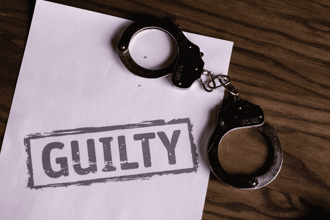 "Pair of handcuffs on a piece of paper that reads ""guilty"""