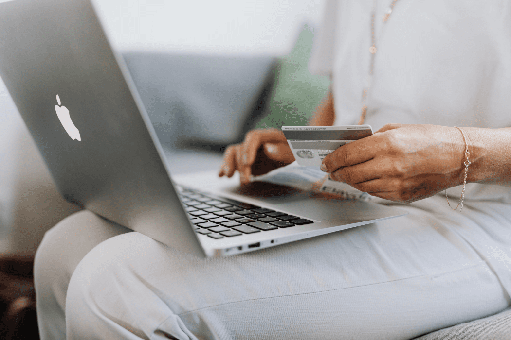 Person on a silver laptop paying for a product with a credit card