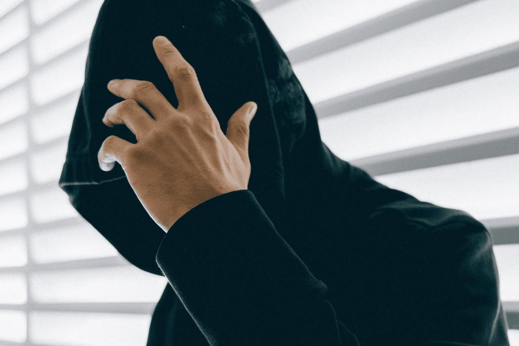 Man in dark hoodie covering face