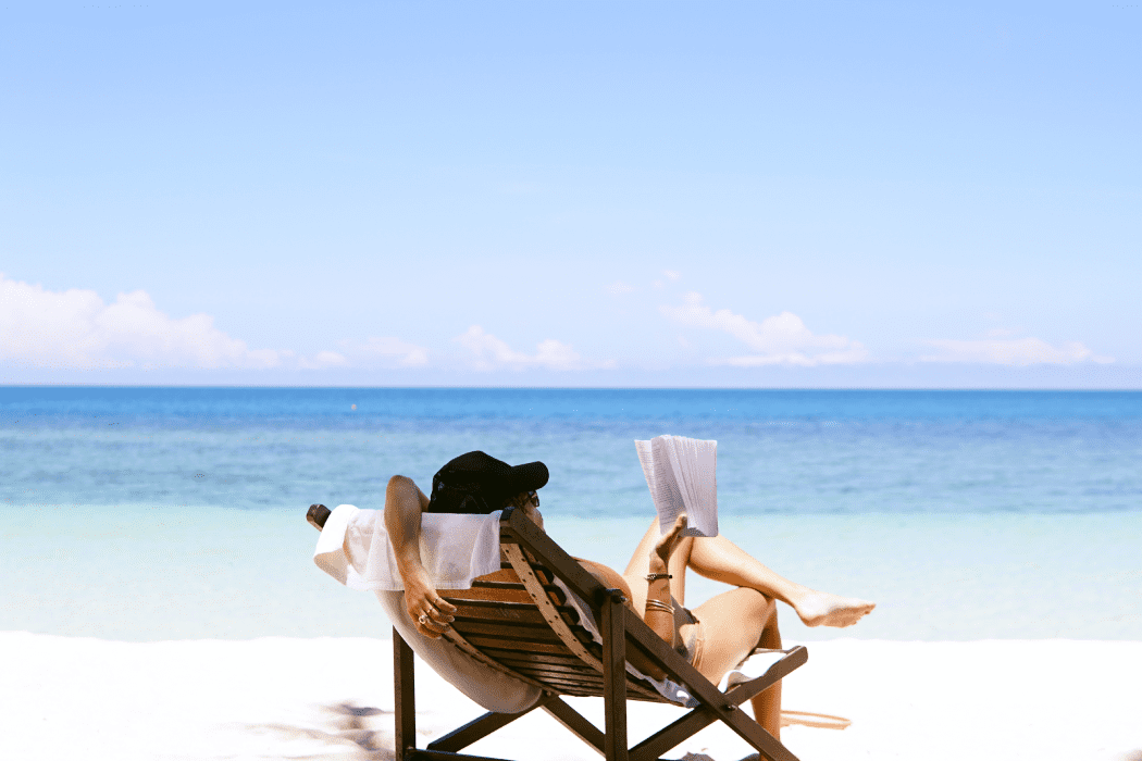 Woman sitting on a beach reading a book
