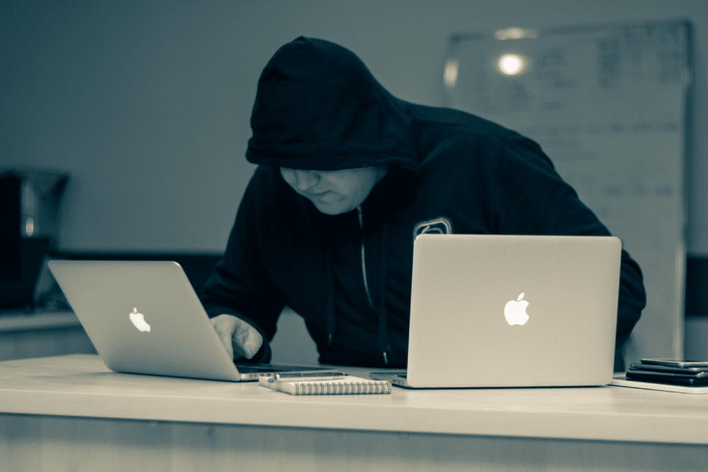 Man in hoodie working on two apple laptops
