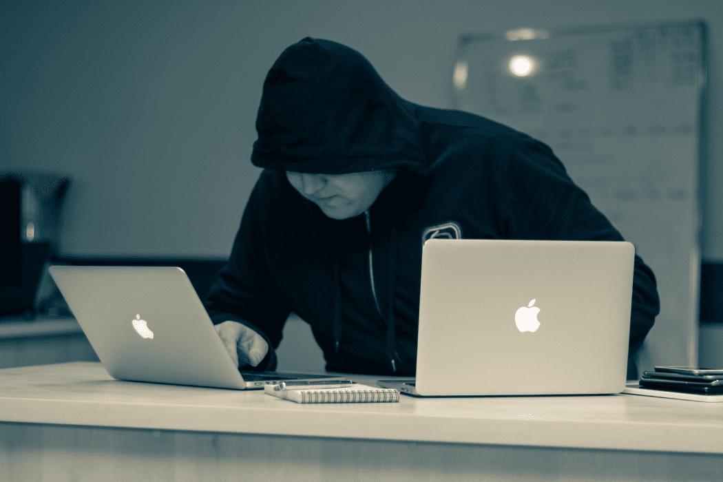 Man in hoodie working on two apple laptops