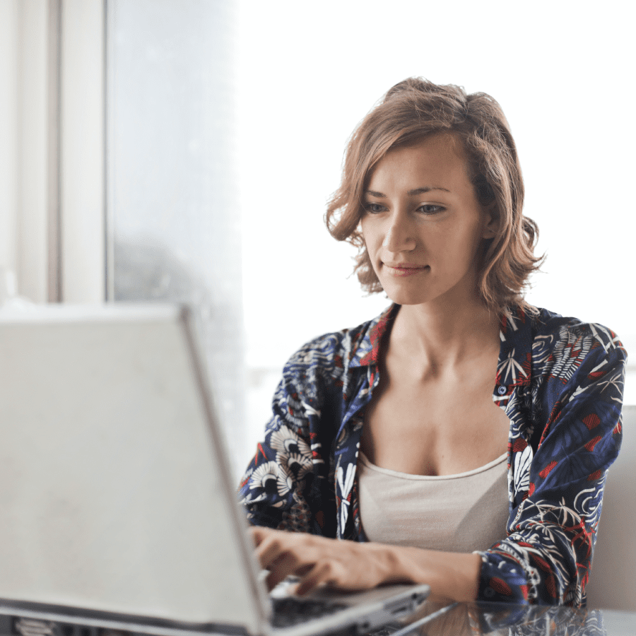 Woman sitting down working on her laptop