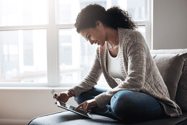 Woman sitting on couch using a tablet
