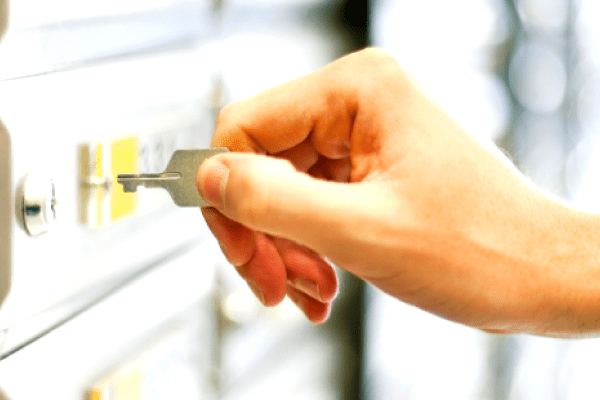 Person putting key into safe deposit box lock