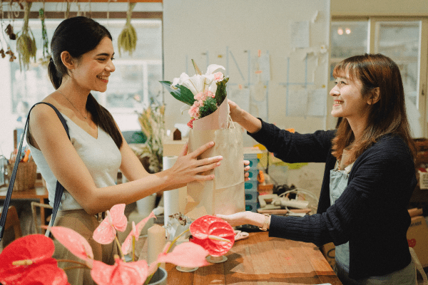 Woman buying flowers from a local shop