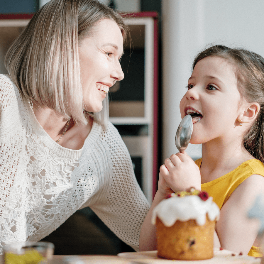 Mother watching her daughter lick a spoon with cupcake icing on it