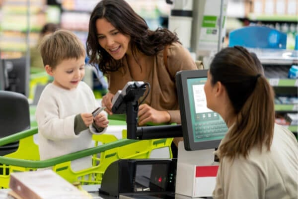 mother and son at a grocery store paying
