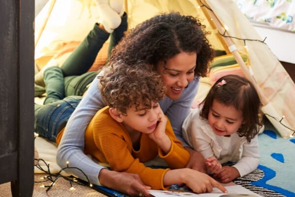 mother and two children sitting in a tent and reading