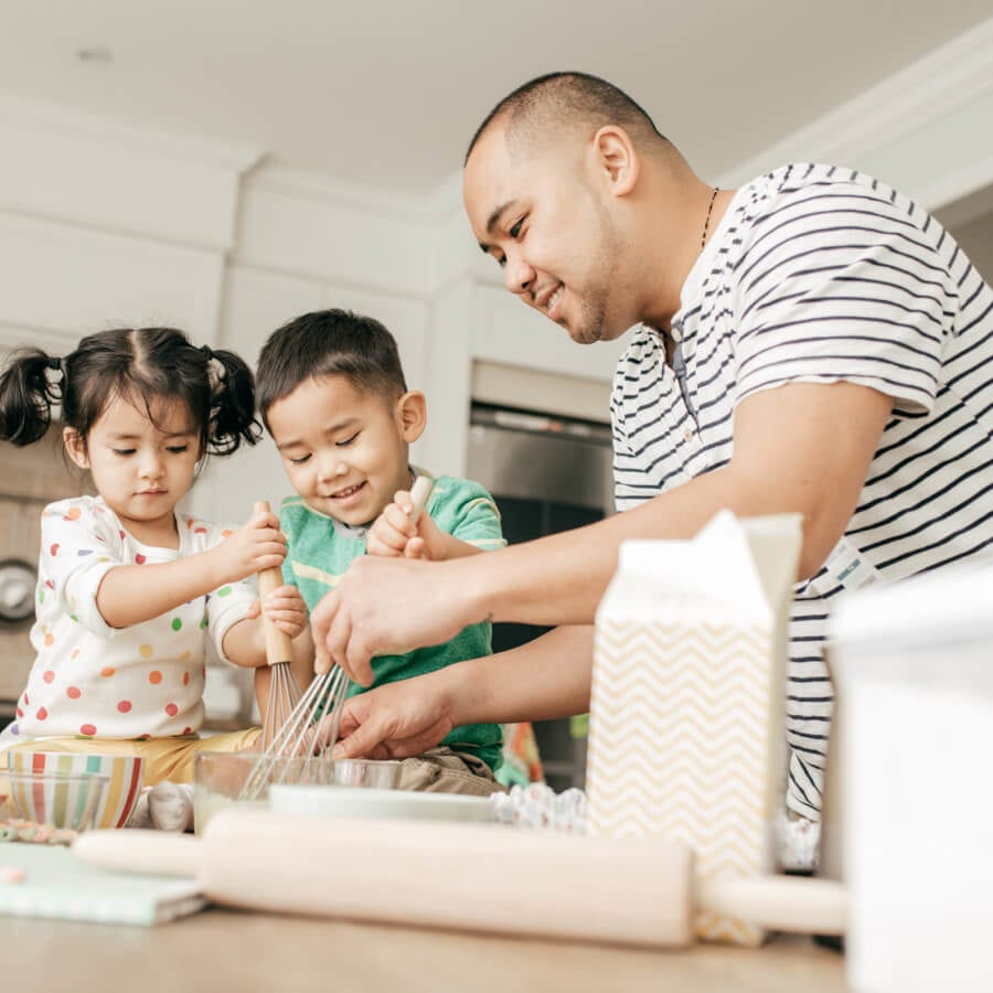 father and two children baking