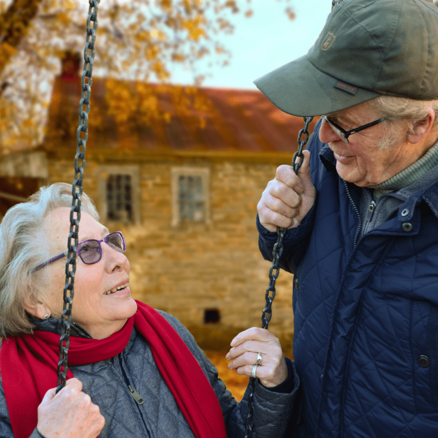 Senior man and woman sitting on a swing